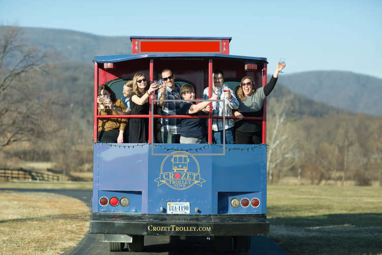 Group enjoying a Charlottesville wine tour from the back of the Crozet Trolley